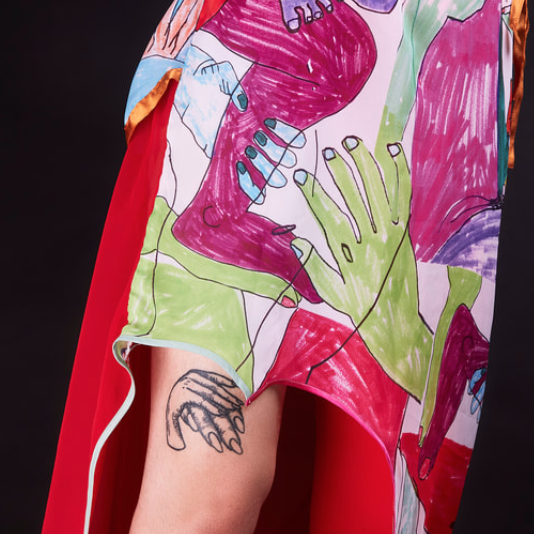 dress with hand-drawn multicolor limbs, wearers bare leg is visible with a black line tattoo of two hands